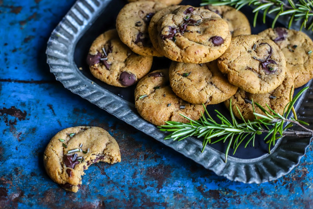 rosemary chocolate chip cookies on small bevelled tray on blue rustic background