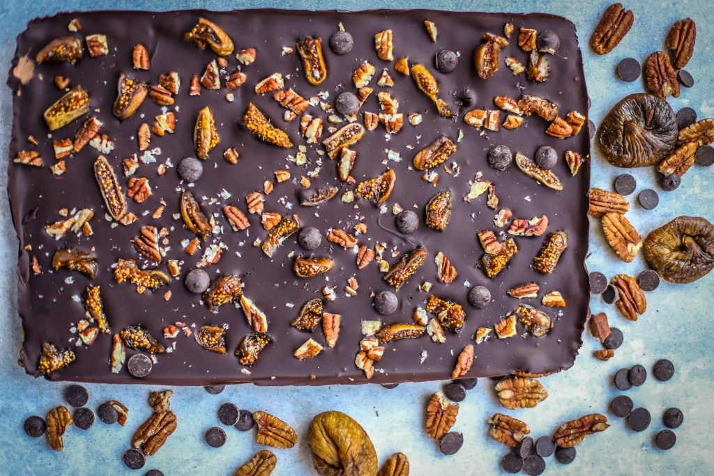 uncut slab of chocolate fig bar with nuts and dried figs surrounding it