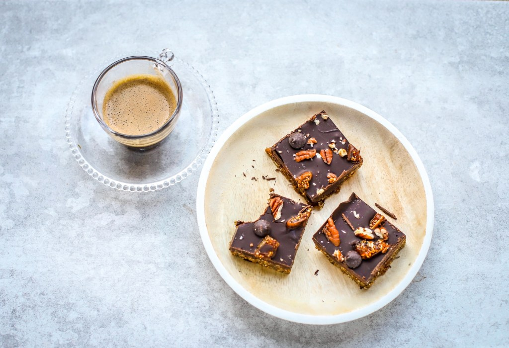 three pieces of chocolate fig and nuts bars on plate with small glass cup of coffee