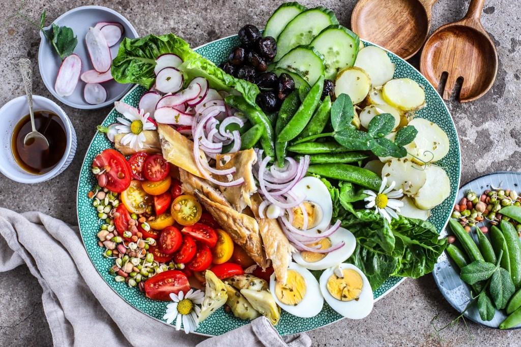 Fully loaded mackerel Niçoise salad on concrete background