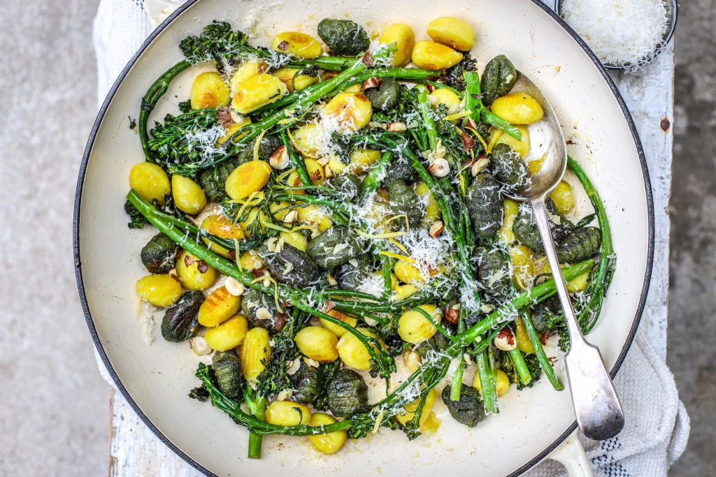 green and yellow gnocchi pasta with broccoli and cheese in wide white dish with spoon