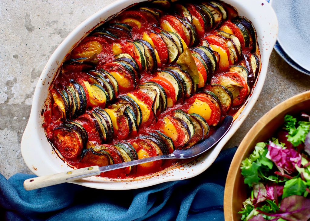 baked ratatouille tian in white oval dish on concrete background