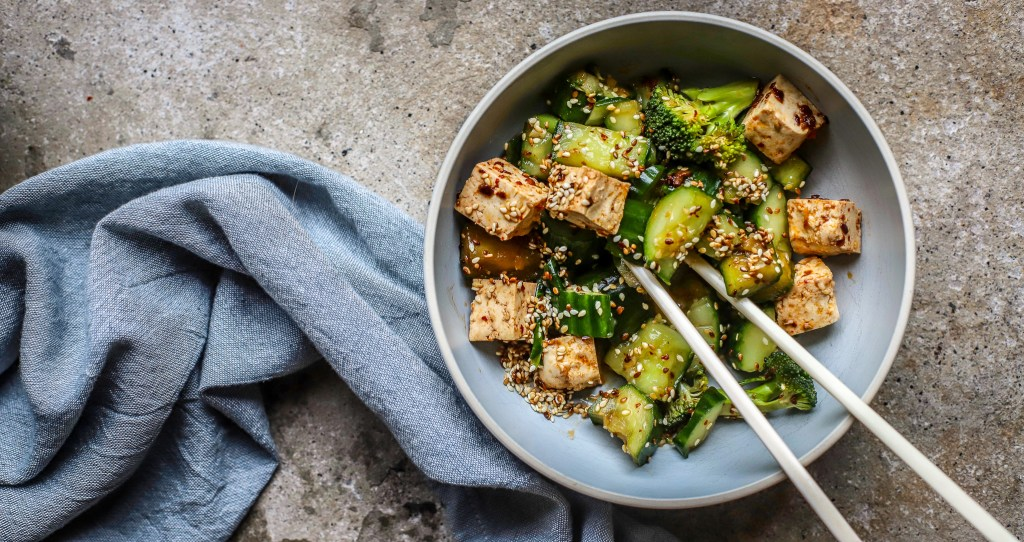 landscape image of cucumber and tofu salad with blue textile