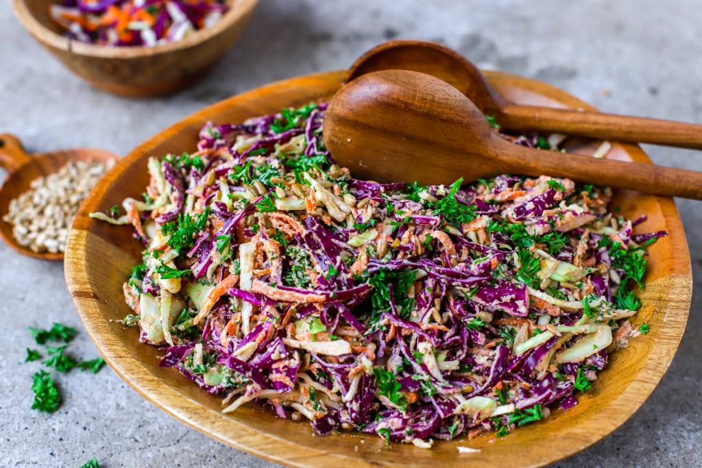 side on view of colorful coleslaw with wooden spoons