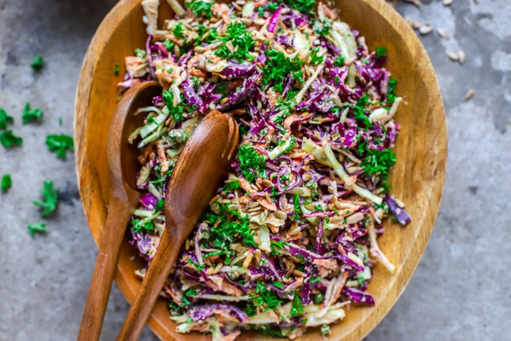 close up of creamy sunflower-ranch coleslaw in assymetric wooden bowl