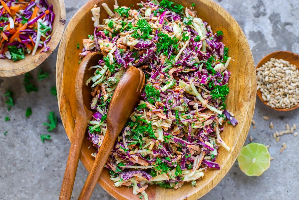 creamy sunflower-ranch coleslaw with wooden spoons in wooden bowl