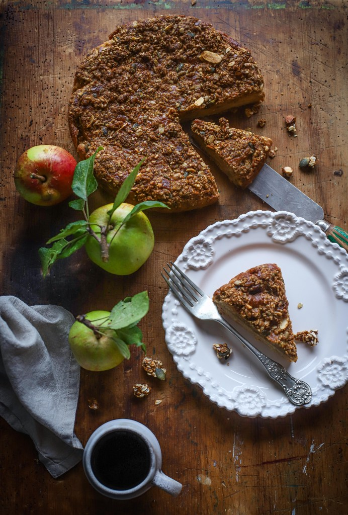 Apple streusel cake sliced on plate with apples