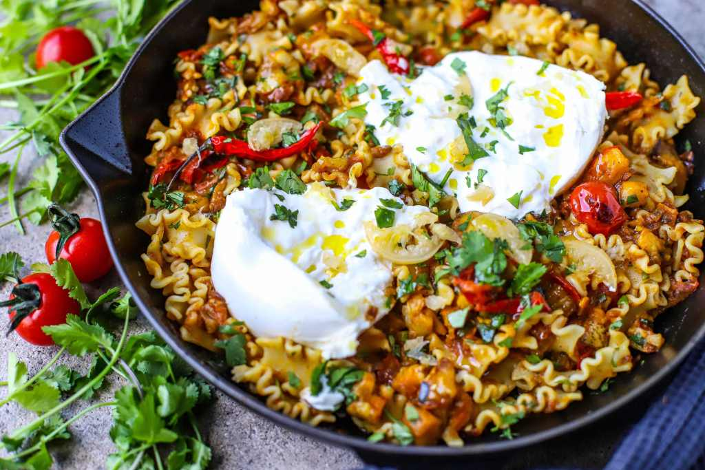 close up of smoky Indian eggplant and pasta in skillet with burrata