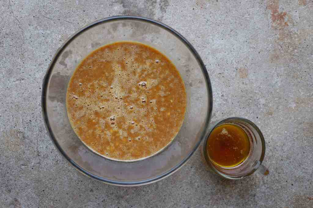 brown butter in cup alongside bowl of banana bread ingredients