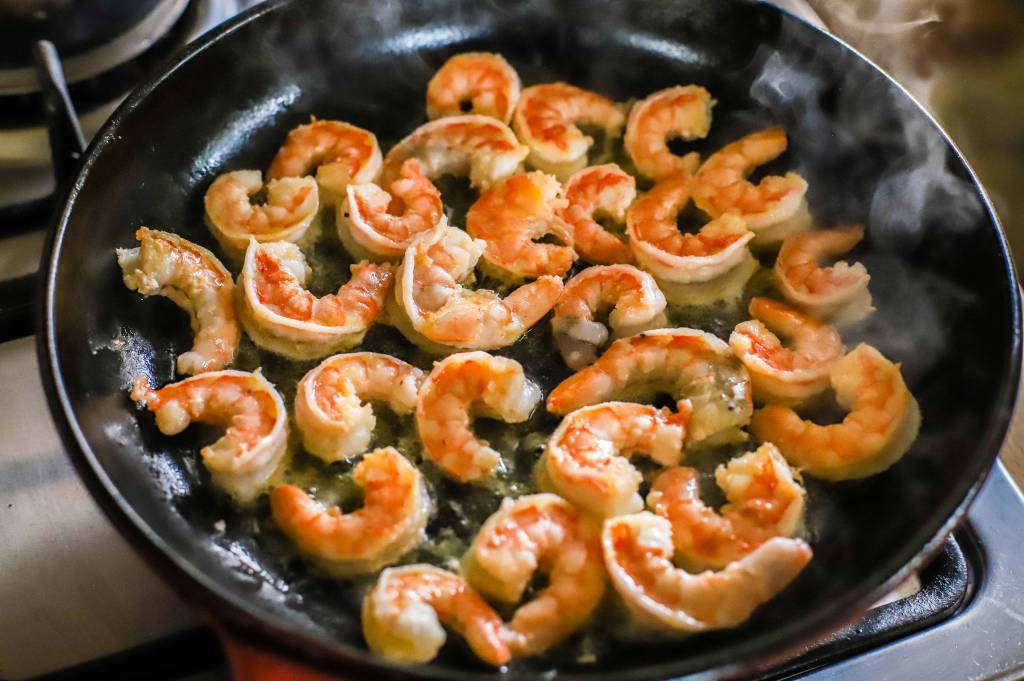 large shrimp frying in cast iron pan