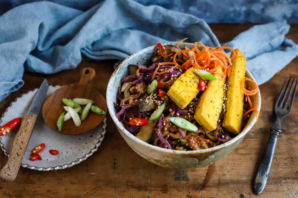 rainbow vegetables and noodles with creamy spicy nut butter sauce