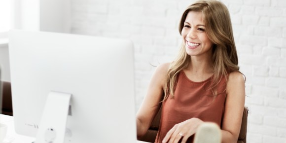 woman with long hair smiling while sitting next to a computer