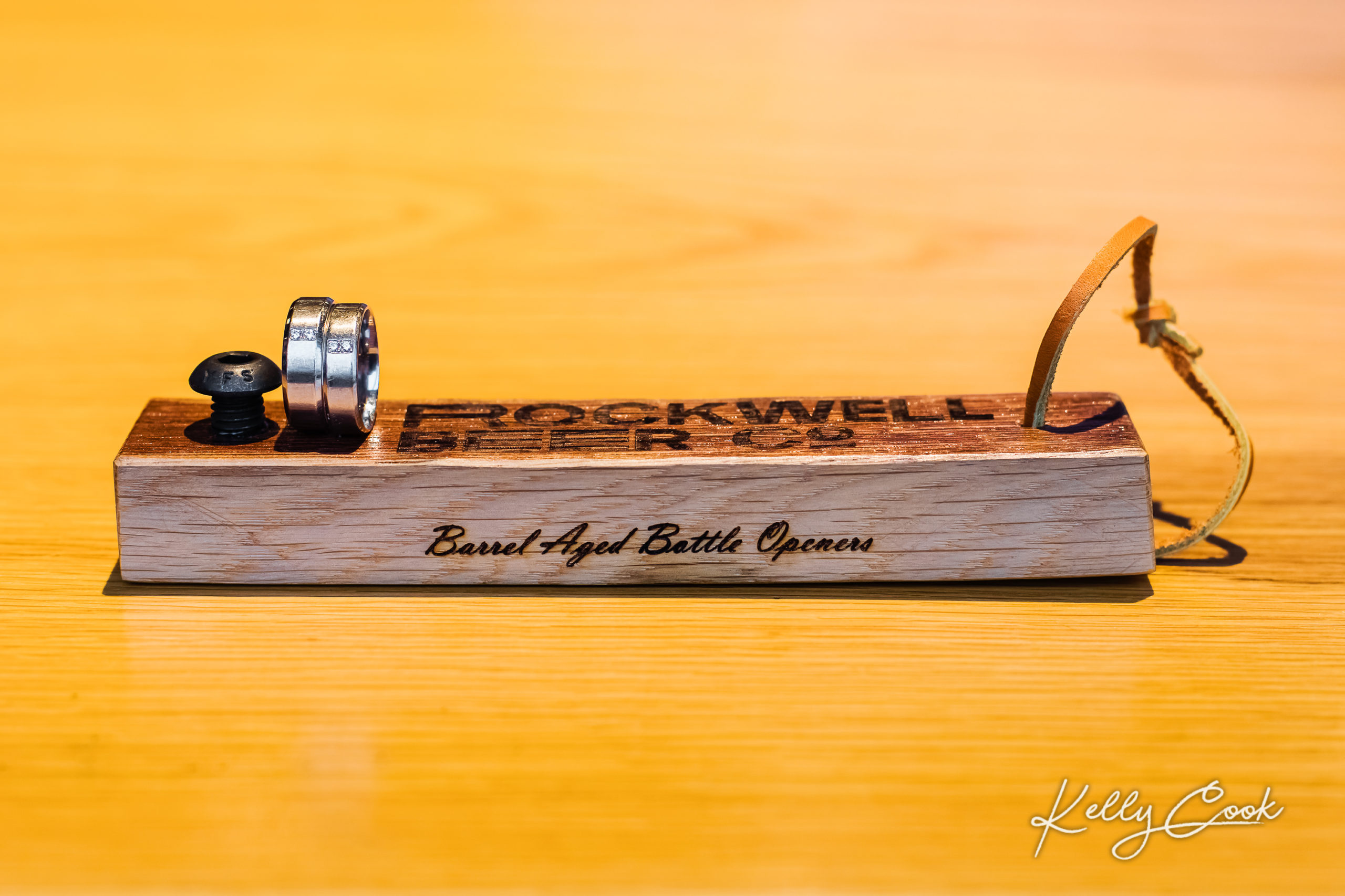 Engagement photo of rings on a brewery bottle opener