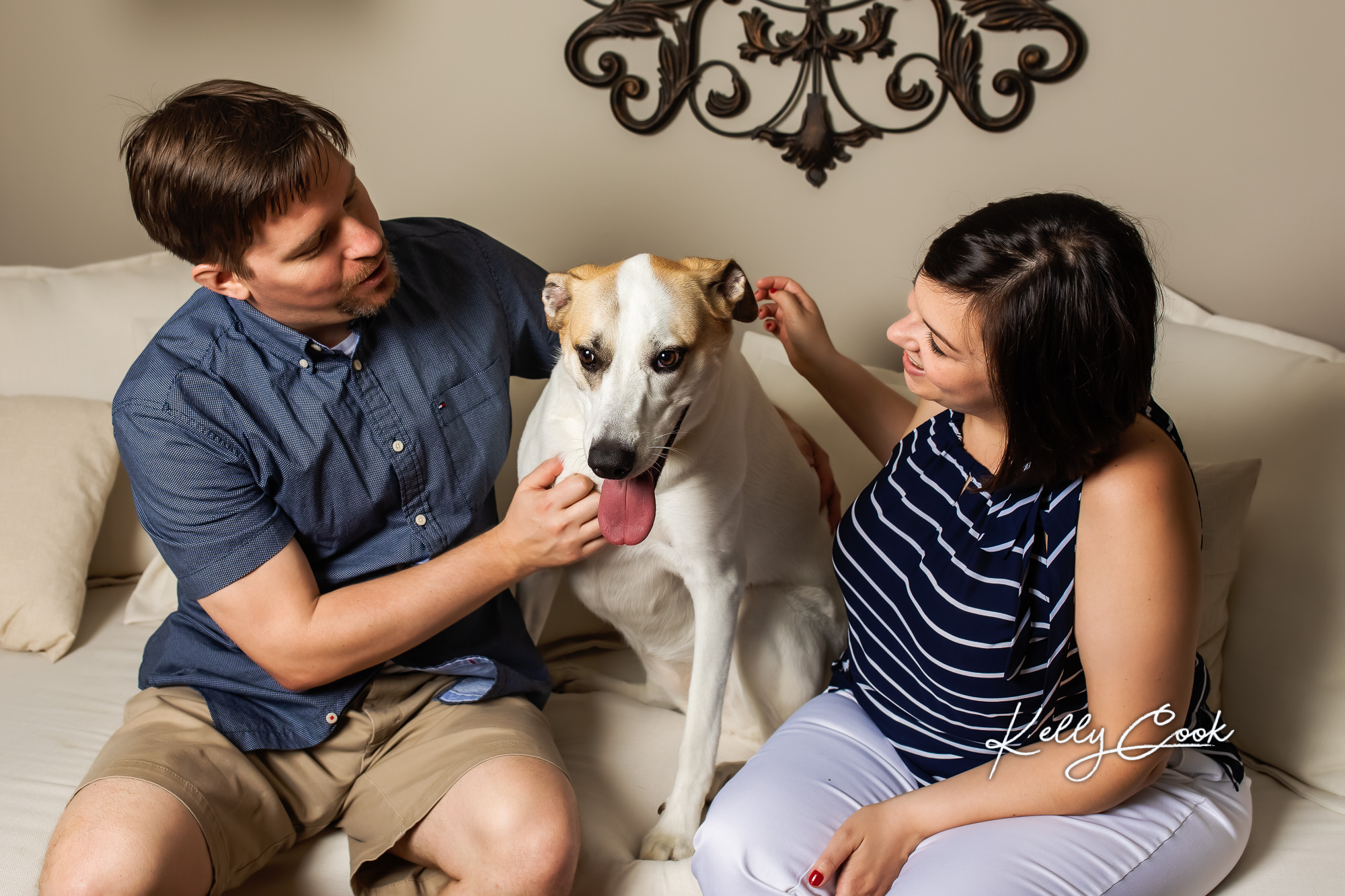Candid lifestyle engagement photo of an engaged couple with their dog