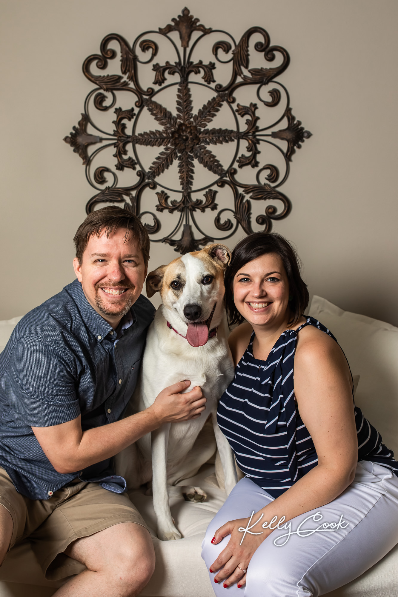 In-home lifestyle engagement photo of an engaged couple with their dog