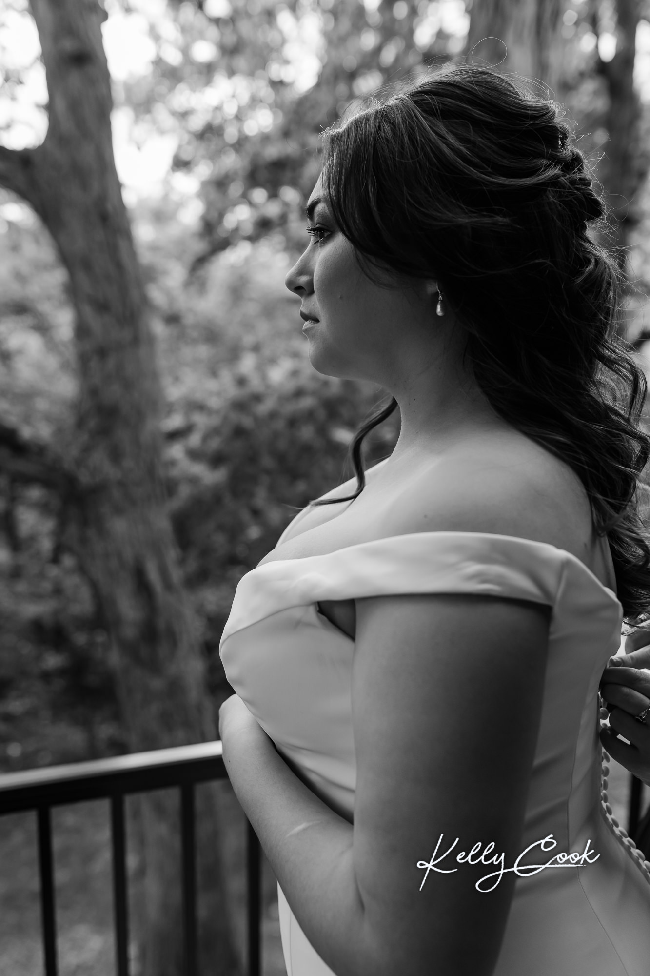 Black and white photo of bride getting her wedding dress buttoned