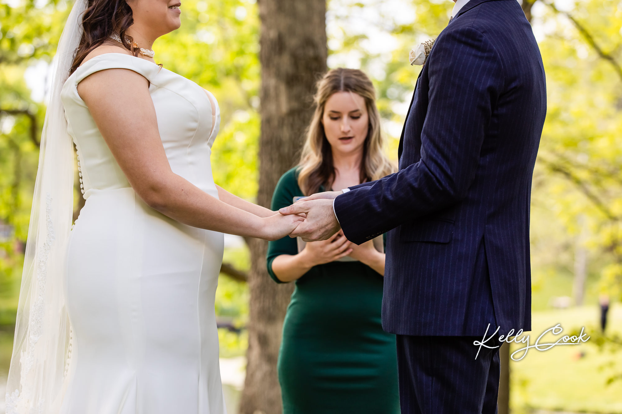 A couple holding hands at their backyard micro wedding in St. Louis