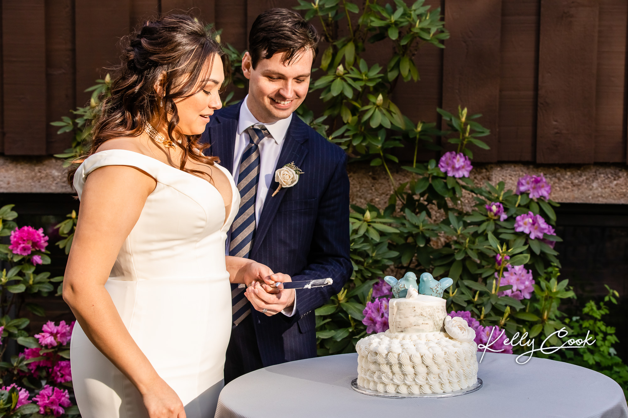 Photo of a couple cutting their cake at their micro wedding in St. Louis