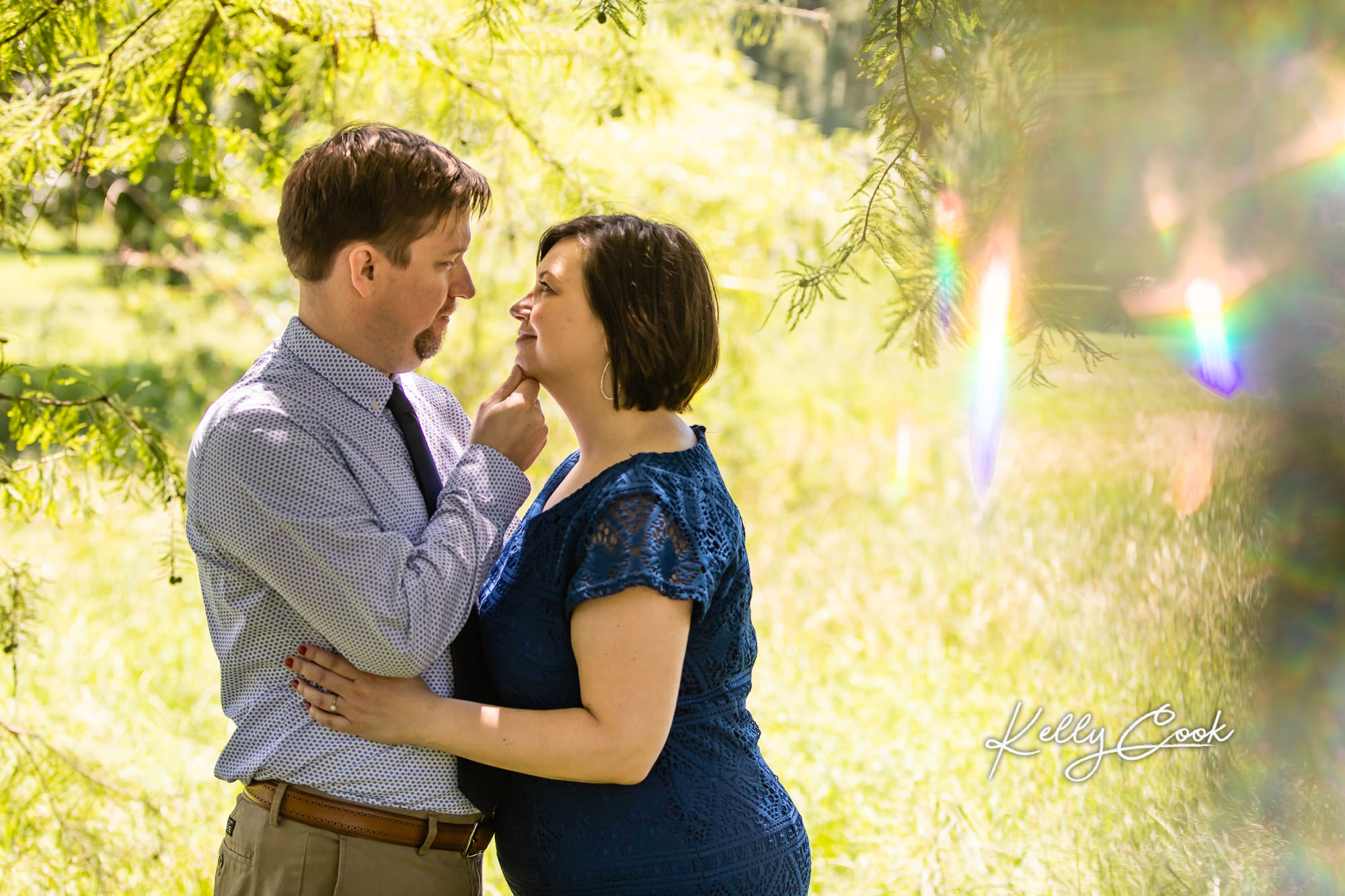 Dreamy St. Louis Engagement photo of an engaged couple embracing in a field in Francis Park