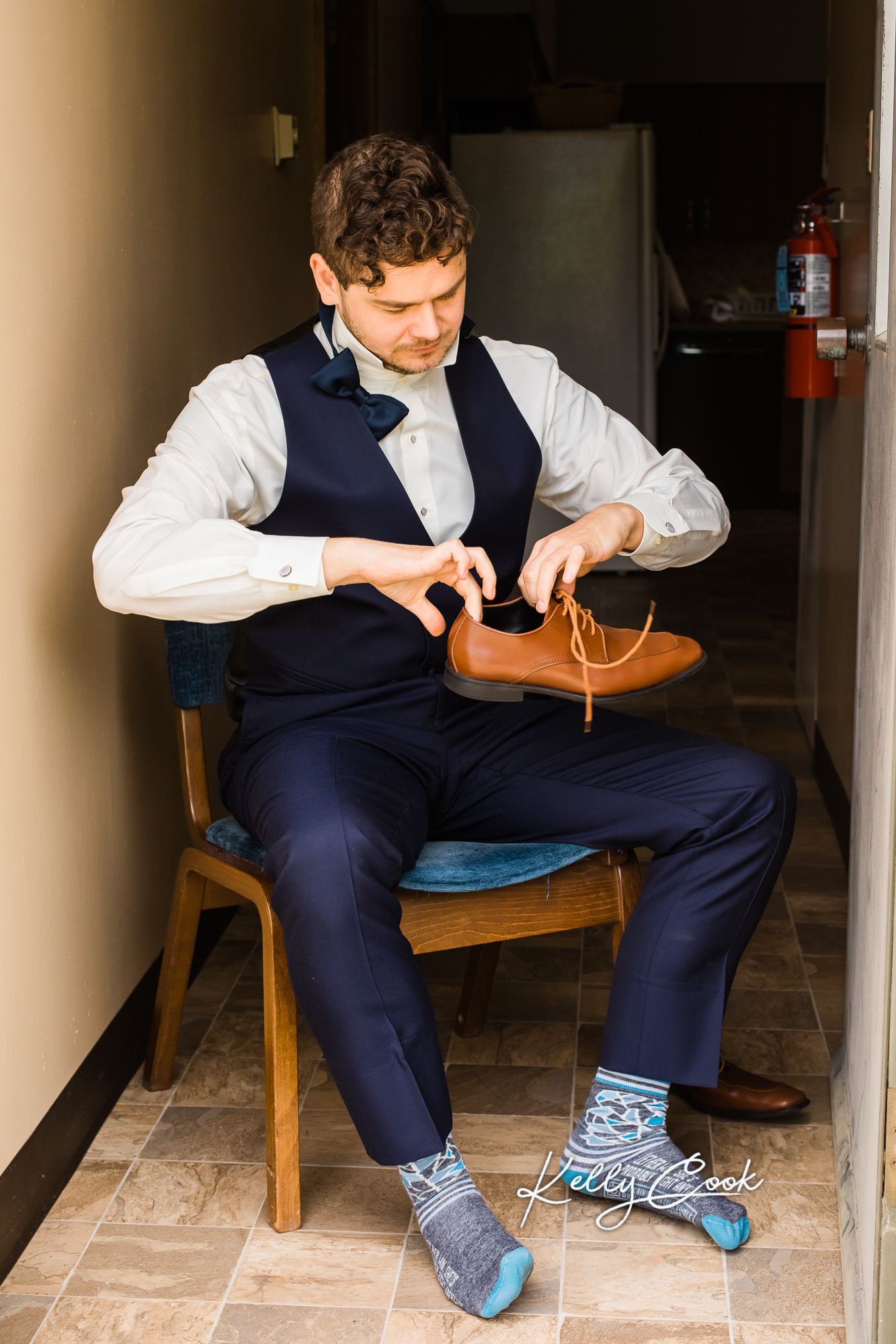 Wedding photo of the groom putting on his shoes
