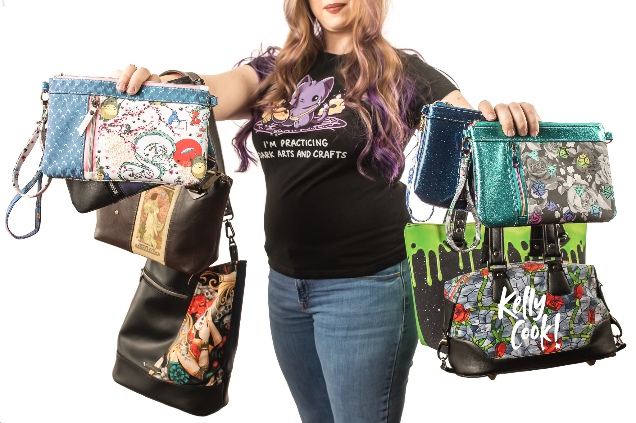 Woman holding a bunch of handmade purses and bags