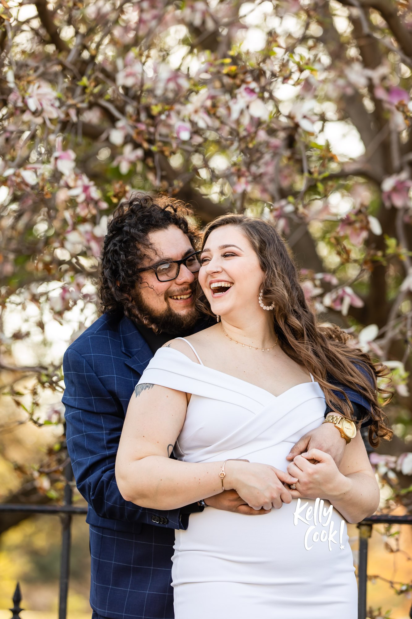 Engaged couple posing for their engagement photos by a magnolia tree in Lafayette Park in St. Louis
