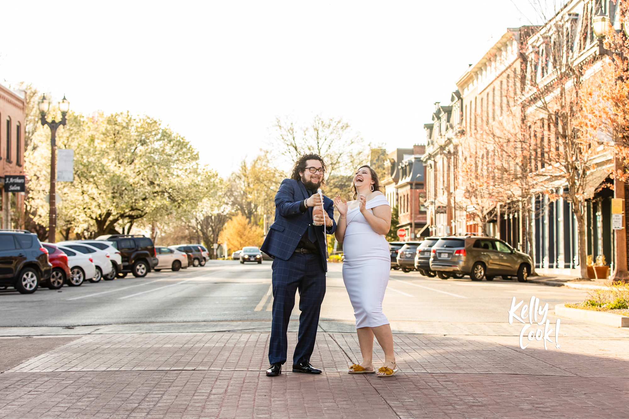 Engaged couple popping Champagne in the middle of a street