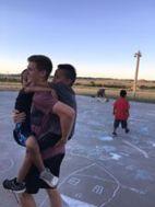 Luke carries two kiddos.