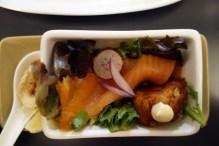 Deep fried calamari ring and smoked salmon salad and a potato croquette
