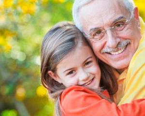 Smiling grandfather hugging his adorable granddaughter