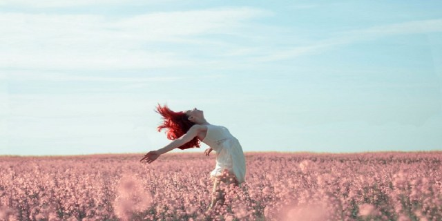 carefree woman in a pink field