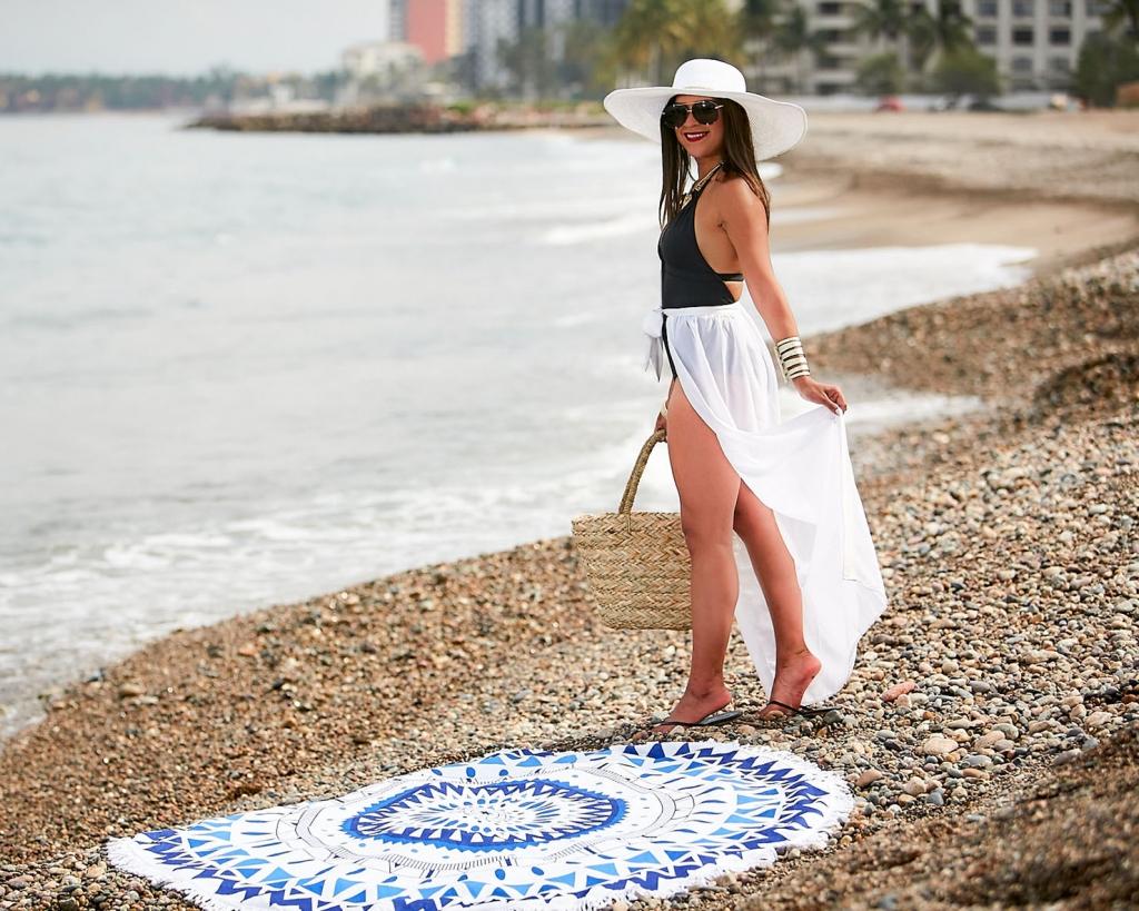 Lifestyle blogger Kelsey Kaplan of Kelsey Kaplan Fashion wearing black one piece swimsuit and round beach towel