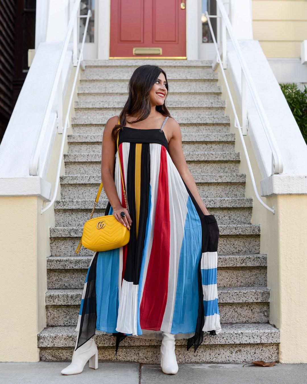 Life style blogger Kelsey Kaplan of Kelsey Kaplan Fashion wearing pleated maxi dress and white Stuart Weitzman booties