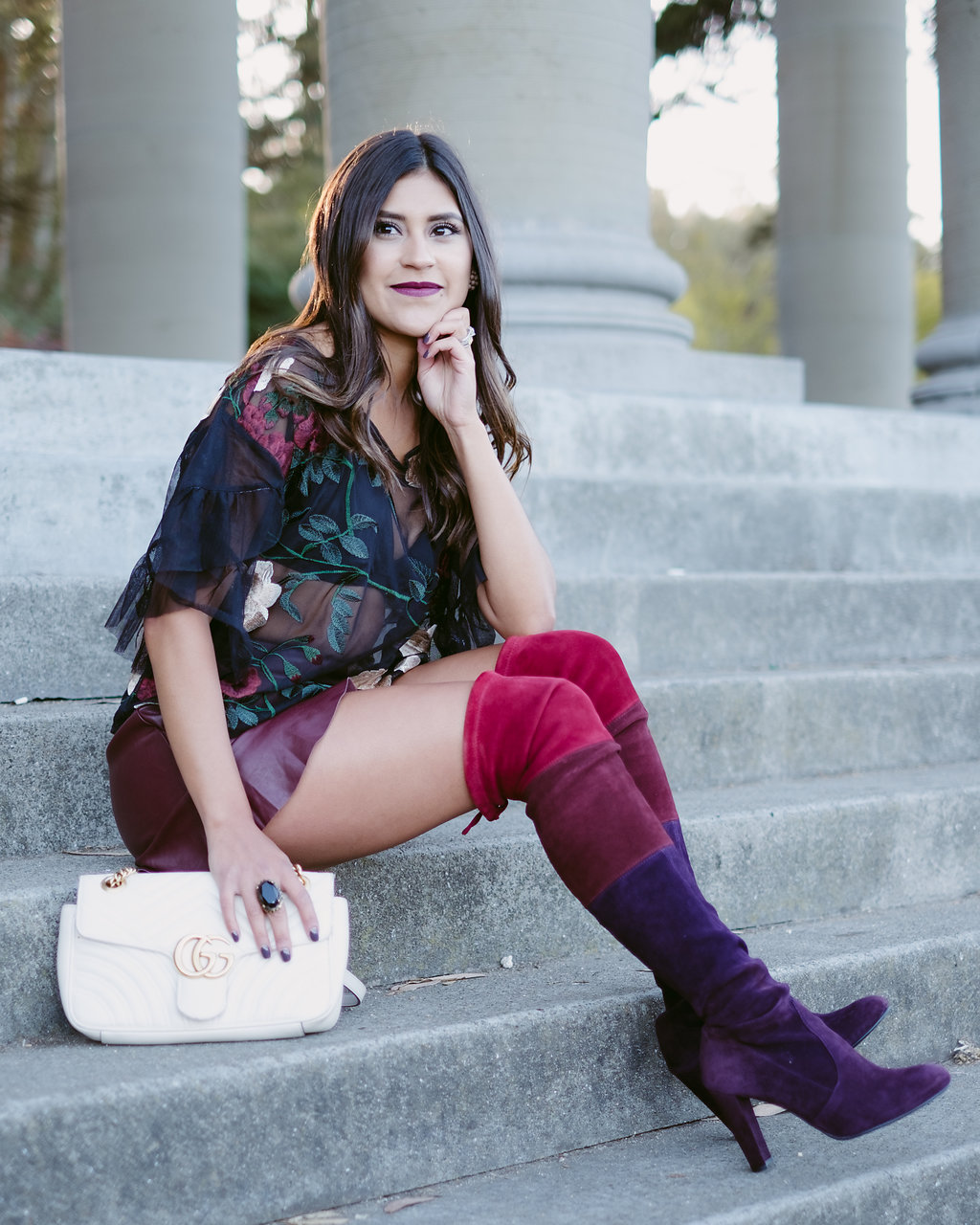 Life style blogger Kelsey Kaplan of Kelsey Kaplan Fashion wearing burgundy faux leather shorts and Stuart Weitzman OTK boots