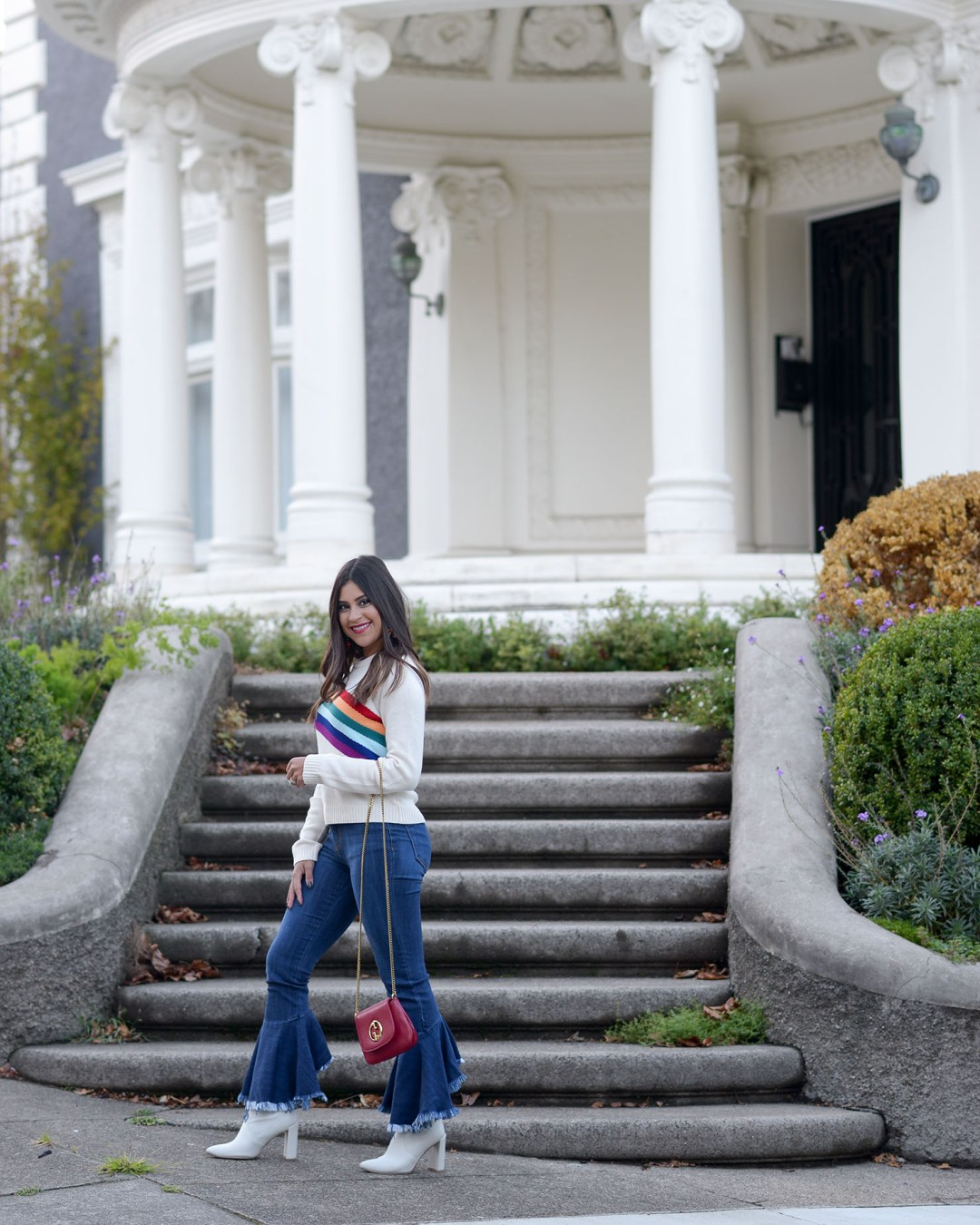Lifestyle blogger Kelsey Kaplan of Kelsey Kaplan Fashion wearing rainbow graphic sweater and Stuart Weitzman Clinger Bootie