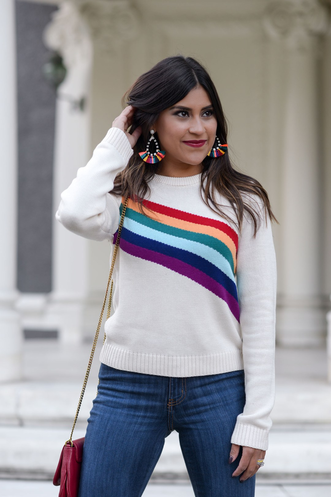 Lifestyle blogger Kelsey Kaplan of Kelsey Kaplan Fashion wearing rainbow graphic sweater and Stuart Weitzman Clinger Bootie and red Gucci purse