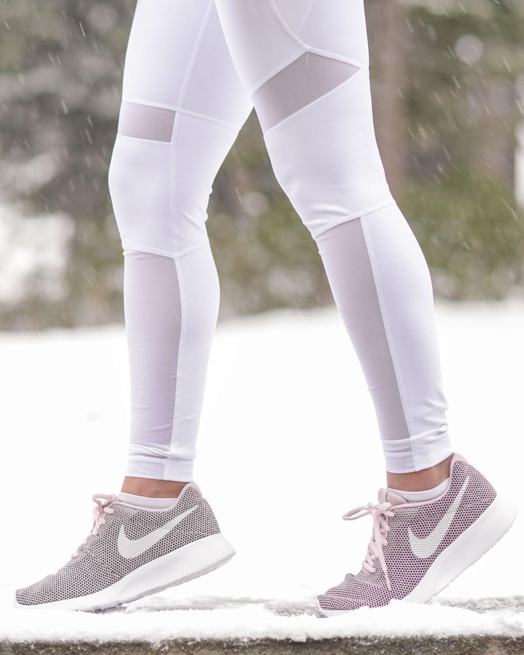 lifestyle blogger Kelsey Kaplan of Kelsey Kaplan Fashion wearing white yoga pants and Nike Tanjun sneakers