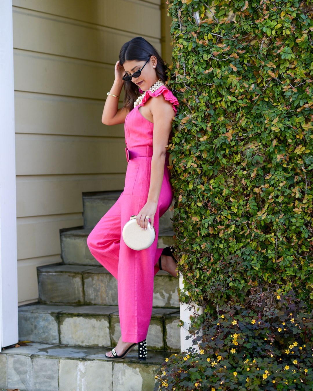 Lifestyle blogger Kelsey Kaplan of Kelsey Kaplan Fashion wearing Pink Belted Jumpsuit and pearl Stuart Weitzman sandals