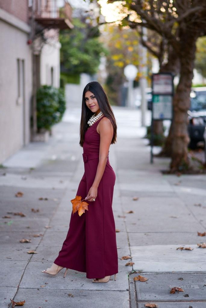 Lifestyle blogger Kelsey Kaplan of Kelsey Kaplan Fashion wearing burgundy jumpsuit and pearl beaded purse