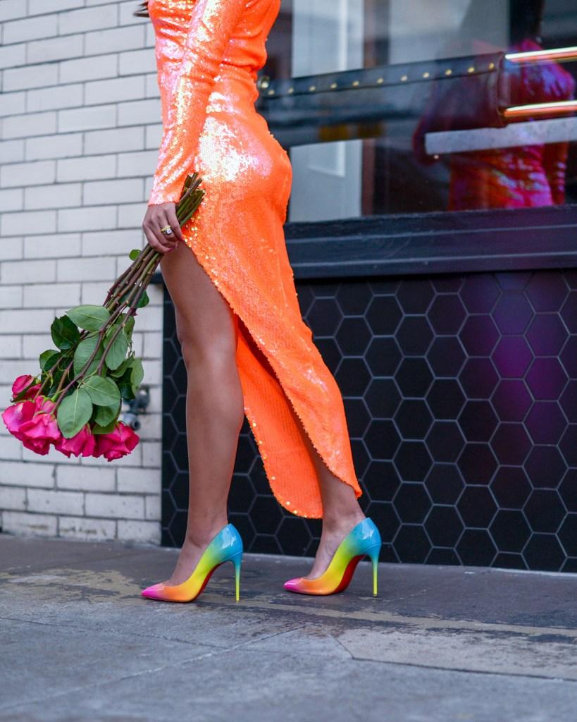 lifestyle blogger Kelsey Kaplan of Kelsey Kaplan Fashion wearing orange sequin dress and rainbow louboutin shoes.
