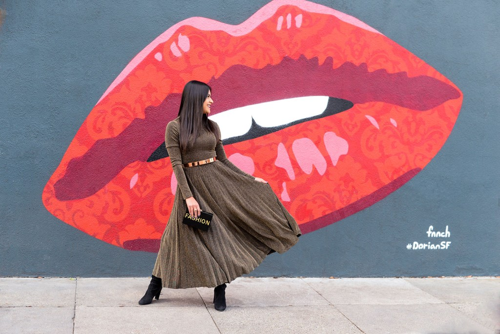 Lifestyle blogger Kelsey Kaplan of Kelsey Kaplan Fashion wearing gold pleated dress and black over the knee boots