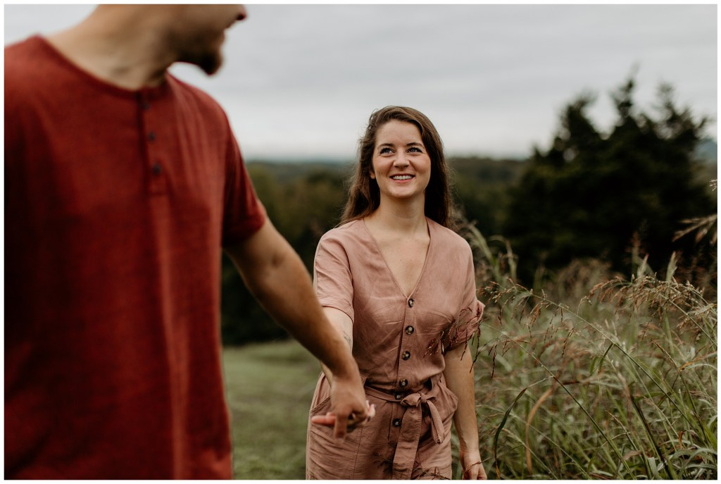 couple holding hands and leading off together in outdoor engagement session