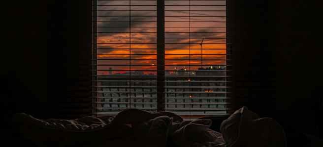 crumpled blanket in dark room at sunset
