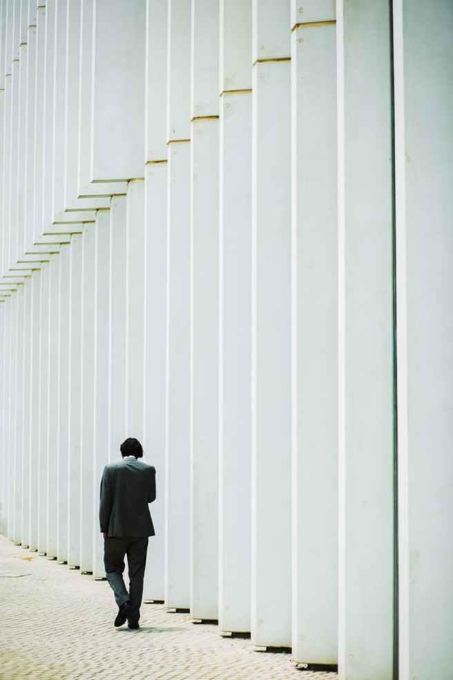 unrecognizable man walking along white building wall