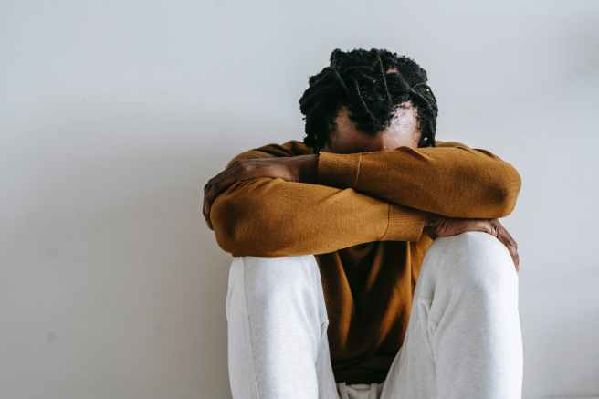 anonymous unhappy black man suffering on light background