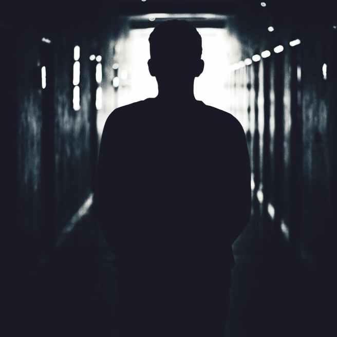 silhouette of man standing on hallway