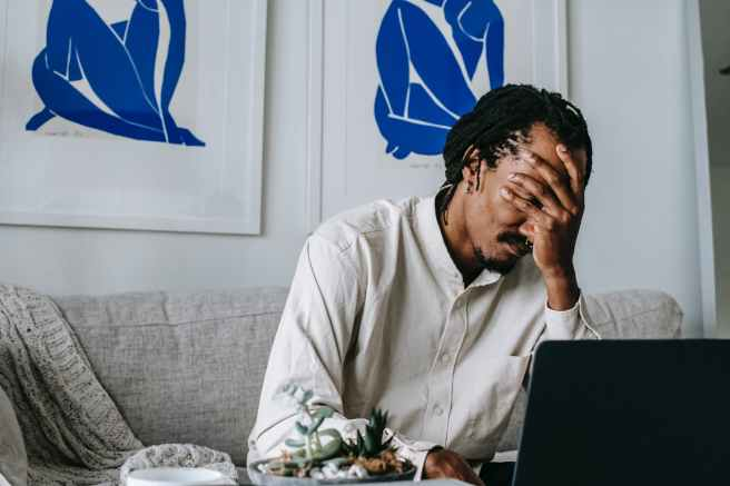 upset young black guy covering face with hand while working remotely on netbook