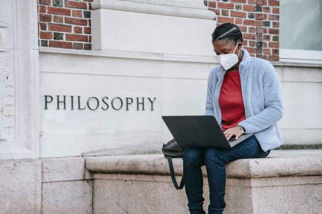 serious young black female student using laptop near university building