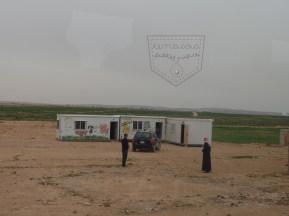 Sekolah kontena di sebuah kem persendirian. Kem Zaatari dapat dilihat dari sini. Kem pelarian persendirian ni dihuni oleh pelarian-pelarian yang tiada dokumen