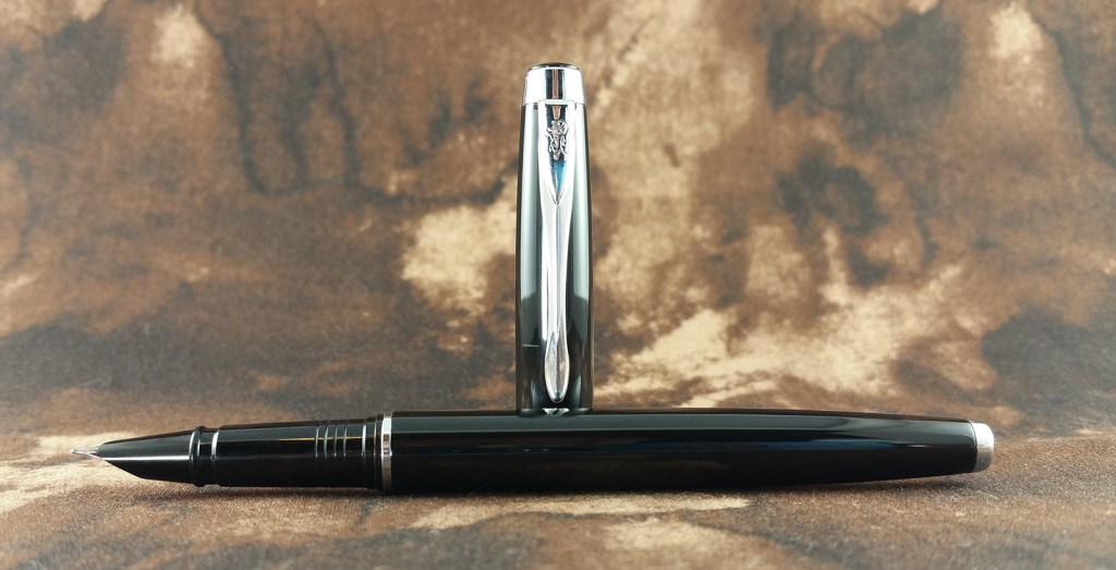 The Jinhao 3005 Fountain Pen, uncapped, with the pen laying down and the cap standing up behind it